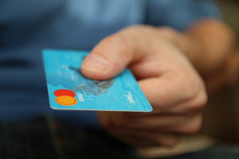 hand holding a light blue credit card